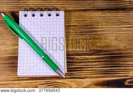 Opened Small Notepad And Ball Pen On Rustic Wooden Table. Top View