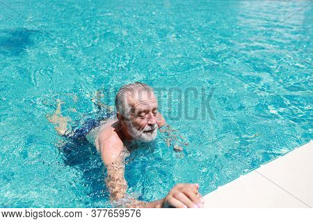 Happy Elderly Caucasian Swimming In Pool During Retirement Holiday With Relaxation And Smiling
