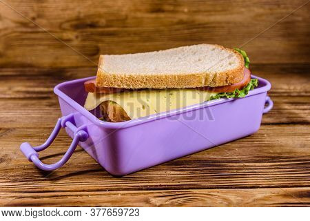 Lunch Box With Sandwiches On Wooden Table
