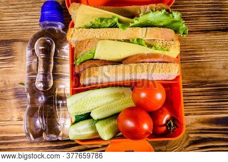 Bottle Of Water And Lunch Box With Sandwiches, Cucumbers And Tomatoes On Rustic Wooden Table. Top Vi