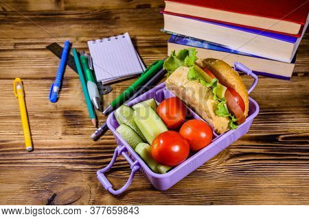 Notepad, Pens, Stack Of Books And Lunch Box With Hamburger, Cucumbers And Tomatoes On Rustic Wooden