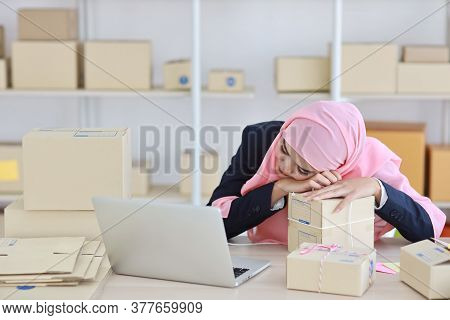 Religious Asian Muslim Woman In Blue Suit And Pink Shaft Frustrated Laid Her Head Down On The Table,