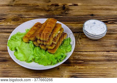 Baked Fish Sticks And Lettuce Leaves In Plate