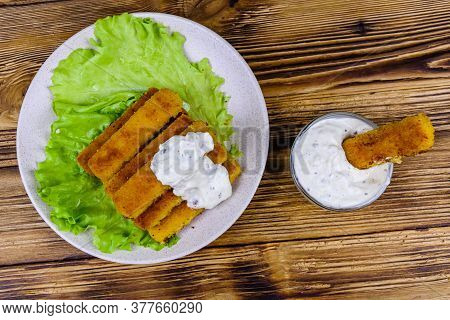 Baked Fish Sticks And Lettuce Leaves In Plate. Baked Fish Stick Dipped Into Sauce In Glass Bowl. Top