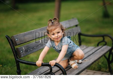 Cute Little Girl In Denim Climbs On The Bench In The Park. Happy Smiled Kid On The Bench