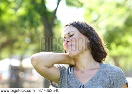 Middle Age Woman In Pain Suffering Neck Ache Standing In A Park At Summer