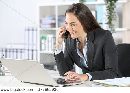Happy Executive Woman Calls Onsmart  Phone Using Laptop Sitting On A Desk At The Office