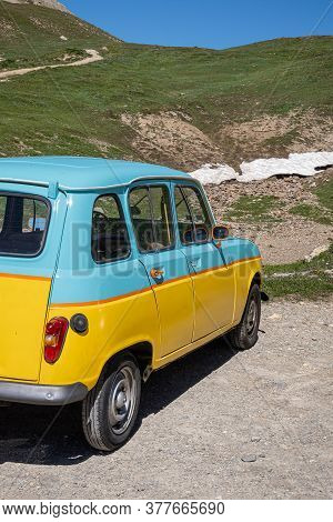 Col Du Galibier, France - July 8, 2020: An Oldtimer Renault 4 Car In Blue And Yellow Colors