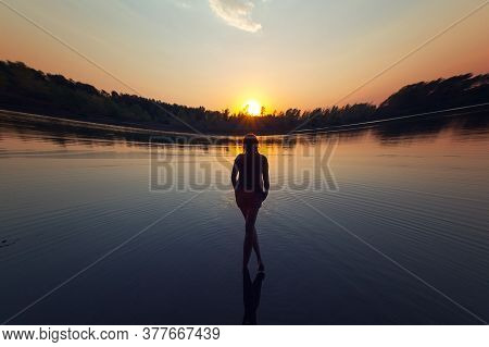 Silhouette Of A Woman In The River At Sunset. Relaxation, Freedom And Solitariness.