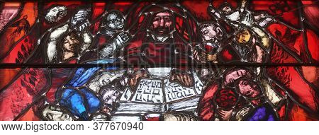PIFLAS, GERMANY - JUNE 07, 2015: God bears the guilt of all mankind, detail of stained glass window by Sieger Koder in church of Saint John in Piflas, Germany