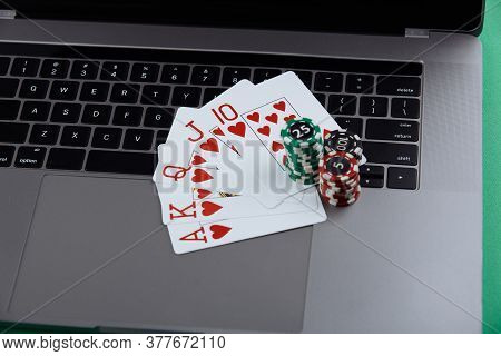 Stacks Of Poker Chips And Playing Cards On A Laptop Computer. Casino And Poker Online Concept