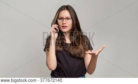 Disturbing Call. Phone Conflict. Annoyed Woman Having Negative Conversation Isolated On Gray. Mobile
