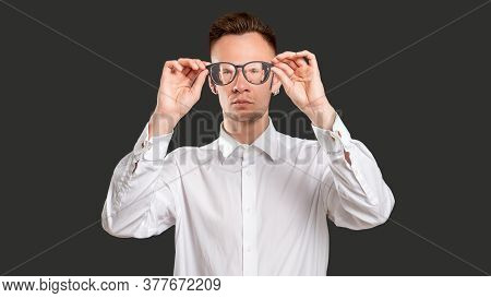 Geek Lifestyle. Optical Illusion. Confident Smart Man Looking Through Eyeglasses With Zoomed Out Per