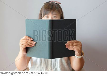 Blurred Asian Female Face Holding And Looking At Book For Reading Template