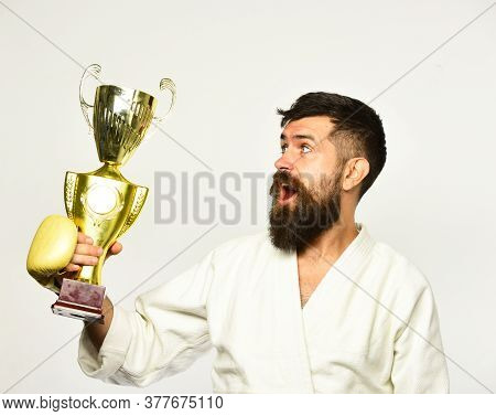Combat Master Celebrates Victory In Competition. Karate Man With Happy Face In Golden Boxing Gloves