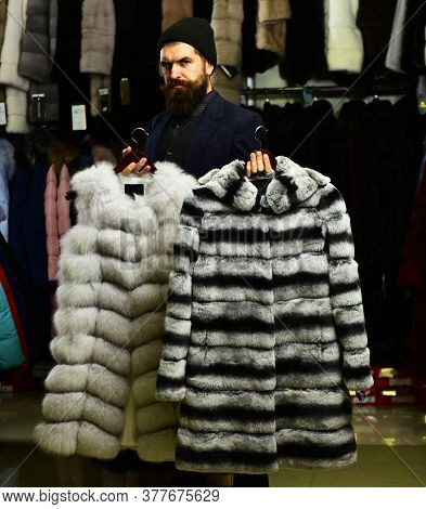 Businessman With Hat And Expensive Overcoats. Customer With Beard Chooses Furry Coats.