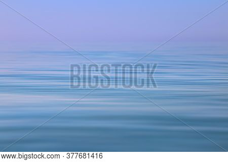 Calm Sea Wavy Surface Of The Sea Under A Clear Sky Close-up. Blue And Purple Background.