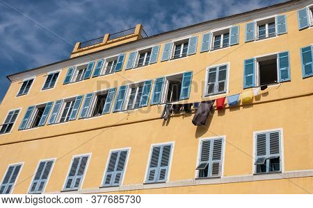 Traditional Colorful Painted Building Facade With Blue Shutters And Laundry Hanging In Bastia, Corsi