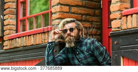 Brutal Male With Blond Hair Irish Architecture Background. Man Casual Fashion. Hipster In Sunglasses