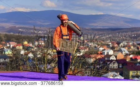 He Loves His Job. Roofer Worker In Special Protective Work Wear. New Roof Under Construction Residen