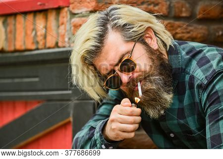 Hipster Smoking Old Architecture Background. Brutal Guy Sunglasses Smoking Tobacco. Smoking Outdoors