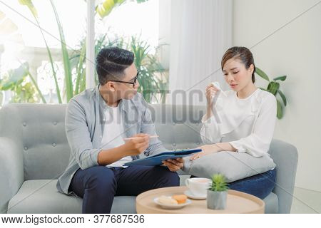 Smiling Young Asian Male Psychiatrist Talking To Young Woman At His Office.