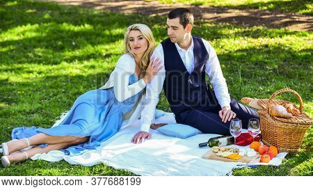 Playful Couple Having Picnic In Park. Couple Cuddling Relaxing At Green Meadow With Picnic Basket. R