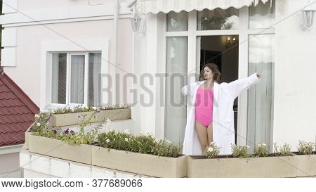 Dark Haired Model In Cotton Bath Robe Puts Her Hands Up On The Balcony In The Morning. Video. Aerial