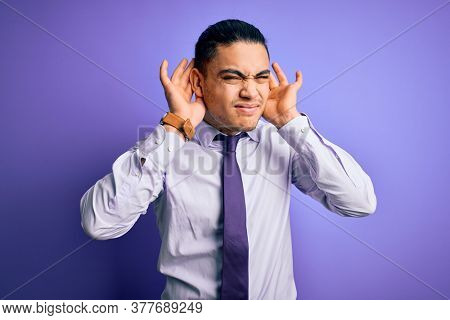 Young brazilian businessman wearing elegant tie standing over isolated purple background Trying to hear both hands on ear gesture, curious for gossip. Hearing problem, deaf