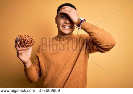 Young brazilian man holding bowl with german salty baked pretzels over yellow background stressed with hand on head, shocked with shame and surprise face, angry and frustrated. Fear and upset