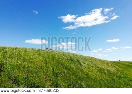 Green Hill And Blue Sky. Two Little Figures On The Top Of A Green Hill On A Sunny Summer Day. White