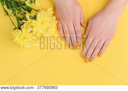 Top View On Manicured Nails. Vibrant Yellow Varnish And Bouquet