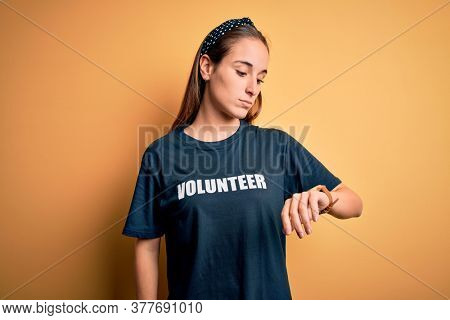 Young beautiful woman wearing volunteer t-shirt doing volunteering over yellow background Checking the time on wrist watch, relaxed and confident