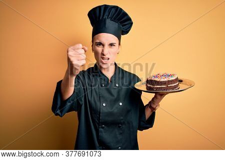 Young beautiful baker woman wearing cooker uniform and hat holding tray with cake annoyed and frustrated shouting with anger, crazy and yelling with raised hand, anger concept