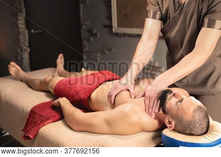 Male Masseur Does A Sports Massage Of The Pectoral Muscle To The Client Athlete In A Professional Ma