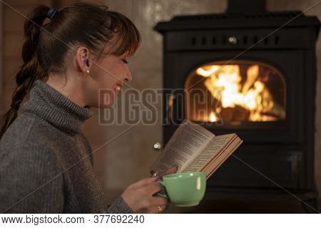 Portrait Of Young Woman Resting With Cup Of Hot Drink And Reading Book Near Fireplace. Cozy Home Chr