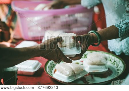 Providing Free Food To The Poor : Volunteers Scooping Out Food To Give Charity To Those Who Are Hung