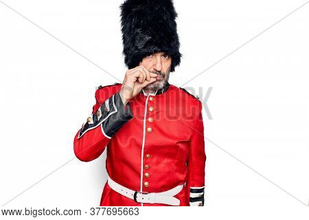 Middle age handsome wales guard man wearing traditional uniform over white background mouth and lips shut as zip with fingers. Secret and silent, taboo talking