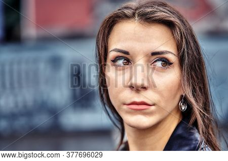 Girl Of Brunette  In A Black Leather Jacket  On A Walk In A Cloudy Summer Evening.  Close-up Of The