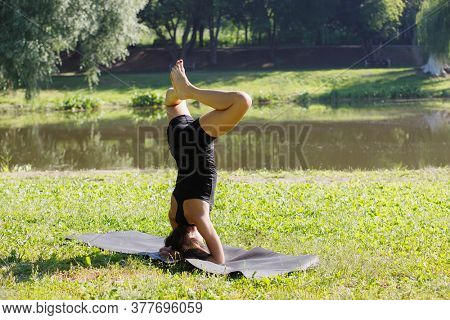 Young sporty attractive woman practicing yoga, doing headstand exercise, variation of baddha konasana in sirsasana pose, working out, wearing black sportswear, in the park. Back view