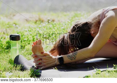 Young woman practicing yoga, doing Head to Knee Forward Bend exercise, Janu Sirsasana pose, working out in nature. Close-up.