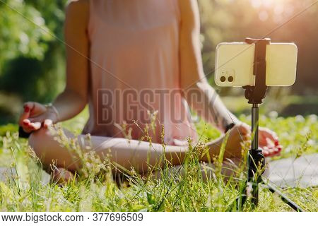 Caucasian female vlogger outdoors, in nature demonstrating exercises for her online blog recording with a camera. Selective focus on foreground, background image. Close-up.