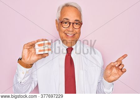 Middle age senior grey-haired dentist man holding prosthesis denture over pink background very happy pointing with hand and finger to the side