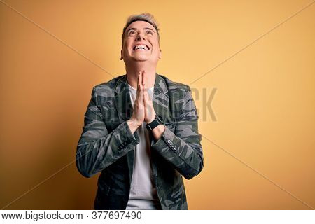 Young handsome modern man wearing business jacket standing over yellow isolated background begging and praying with hands together with hope expression on face very emotional and worried. Begging.