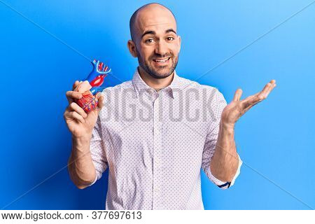 Young handsome bald man holding plastic organ heart celebrating achievement with happy smile and winner expression with raised hand