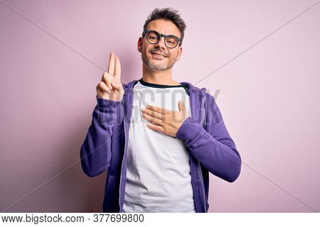 Young handsome man wearing purple sweatshirt and glasses standing over pink background smiling swearing with hand on chest and fingers up, making a loyalty promise oath