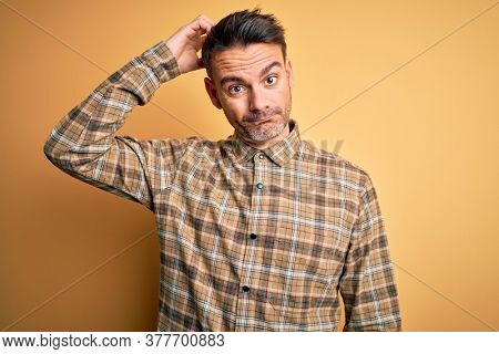 Young handsome man wearing casual shirt standing over isolated yellow background confuse and wonder about question. Uncertain with doubt, thinking with hand on head. Pensive concept.