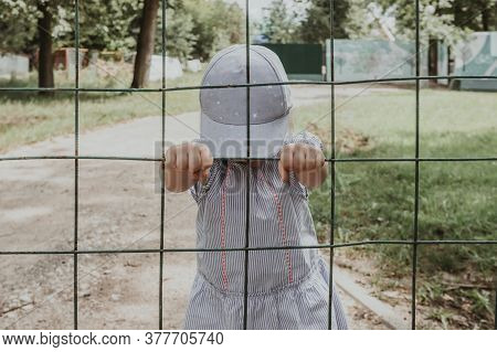 Little Baby Girl Behind Bars. The Child Stands With His Head Tilted And Holds His Hands On The Bars