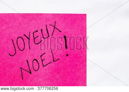 Joyeux Noel (merry Christmas) Handwriting Text Close Up Isolated On Pink Paper With Copy Space. Writ
