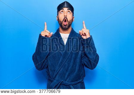 Young hispanic man wearing sleep mask and robe amazed and surprised looking up and pointing with fingers and raised arms.
